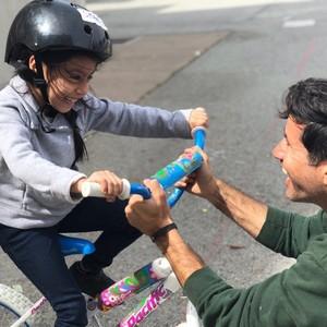 Kian teaching a child to ride a bike